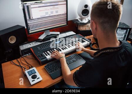 Playing midi keyboard. Sound engineer working and mixing music indoors in the studio