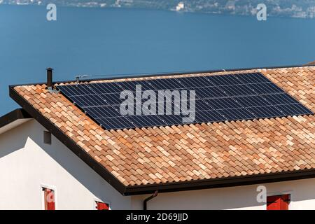 Solar panels on the roof of a house with a blue lake on the background. Renewable energy concept