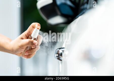 Closeup car wash clening using hand spraying alcohol, disinfectant spray on car door handle for safety prevent and protect from infection of virus