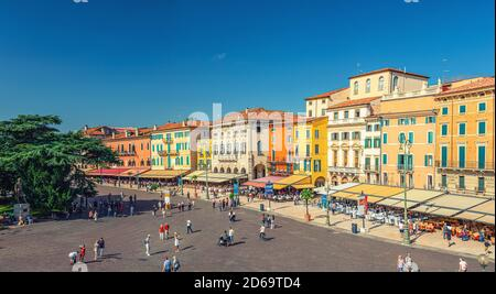 Verona, Italy, September 12, 2019: panorama of Piazza Bra square aerial view in historical city centre with row of old colorful multicolored buildings cafes and restaurants and walking tourists - Stock Photo