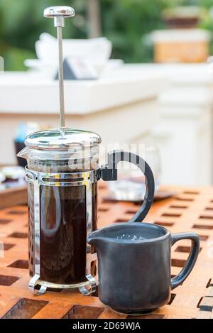 drinks, energetic, morning and caffeine concept - cup of black coffee and french press on table at restaurant.