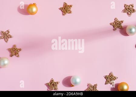 Creative Christmas frame from handmade stars, shiny small golden and silver spheres on a pastel pink background, copy space. Flat lay. Congratulation - Stock Photo