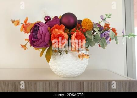 Artificial flowers in a white vase on a shelf in the room. Fabric flowers as an element of interior decor. Artificial peonies, a bouquet of flowers in - Stock Photo