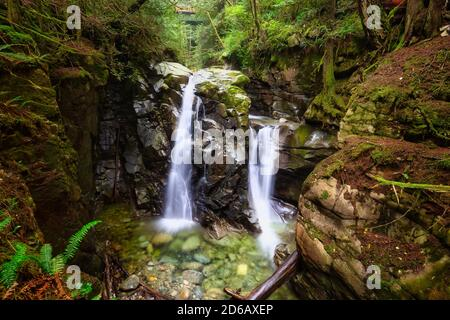 Beautiful view of water cascading in a canyon surrounded by green nature - Stock Photo
