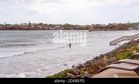 Yeppoon, Queensland, Australia - december 2019: A woman emerges from the ocean after her swim at high tide on the beach