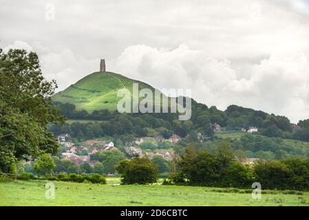 Fluffy white clouds frame Glastonbury Tor in the summer. Farmland frames the foreground, with the red roofs of Glastonbury town in the center valley.