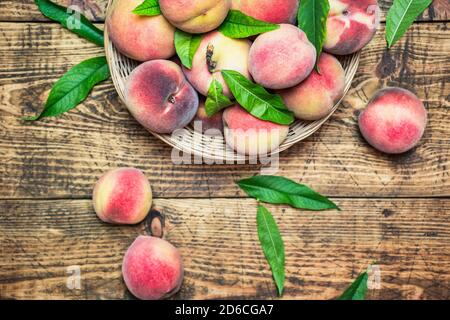 Ripe fresh peaches in a basket on a rustic wooden table, top view. Healthy organic fruit. Stock Photo