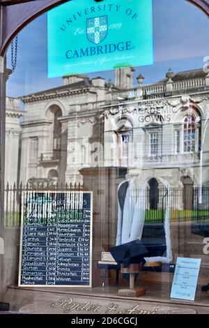 Shop window of Ryder & Amies (seller of academic gowns) with reflection of Senate House, university of Cambridge, England.