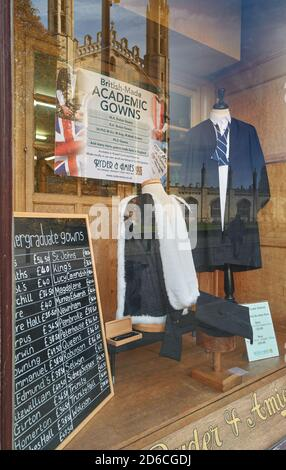 Shop window of Ryder & Amies (seller of academic gowns) with reflection of King's college, university of Cambridge, England.