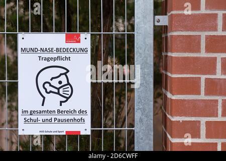 Nuremberg, Germany - October 15, 2020: Sign at fence of school informing about Mund - Nase Bedeckung Tragepflicht im gesamten Bereich des Schul- und P