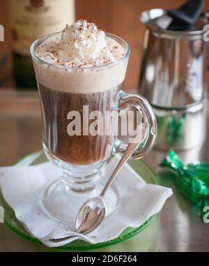 Close-up Irish coffee beverage in transparent glass with whipped cream and blurred background.  Irish Whiskey. Studio shot. Indoors.