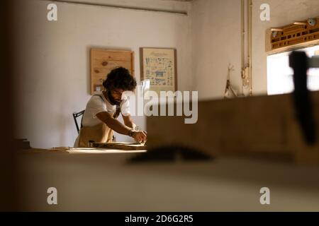 Hispanic man working as carpenter in a small wood laboratory. Bearded man concentrated on shaping a new piece of timber for a home furniture in his ca