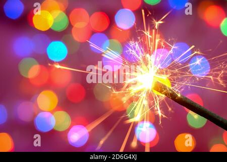 Bright burning sparkler against the backdrop of defocused multicolored garland. Blurred backdrop. Merry Christmas or birthday holiday concept. Close-u