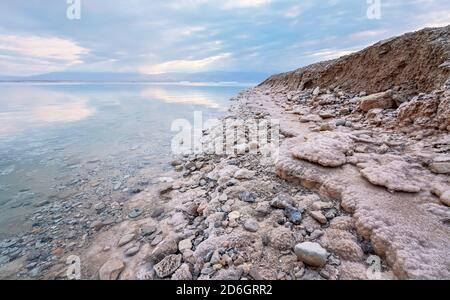 Sand and stones covered with crystalline salt on shore of Dead Sea, clear water near - typical scenery at Ein Bokek beach, Israel Stock Photo