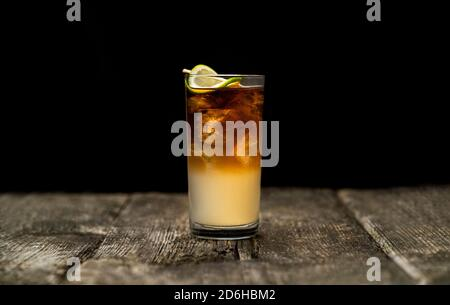 Dark and Stormy cocktail in high ball glass with ice and a lime wedge garnish on an old wooden table with a black background