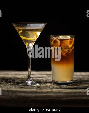 Dark and Stormy cocktail in high ball glass with ice and a lime wedge garnish with a Vodka Martini on an old wooden table with a black background