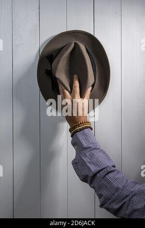 An old hat hanging on a white wooden wall - Stock Photo