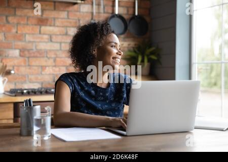 Smiling African American woman look in distance dreaming