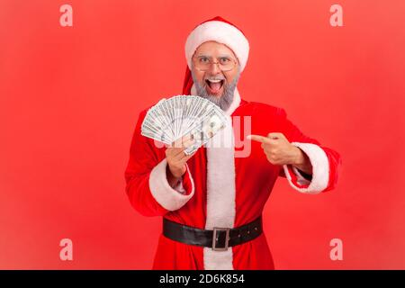 Extremely happy excited man in santa claus costume pointing finger at dollar banknotes he holding in hand looking at camera with big eyes and open mou