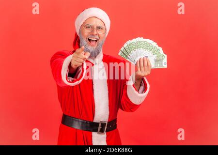 Extremely happy excited santa claus holding fun of euros and pointing finger at you looking at camera, holidays victory. Indoor studio shot isolated o