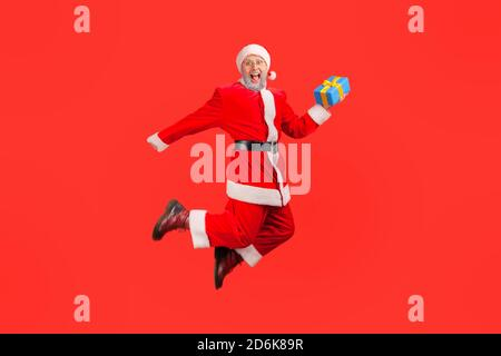 Extremely happy santa claus holding gift box jumping high and looking at camera with toothy smile, satisfied with winter holidays. Indoor studio shot