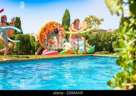 Fun in the pool with boys and girls holding inflatable toys dive into the water during summer outside - Stock Photo