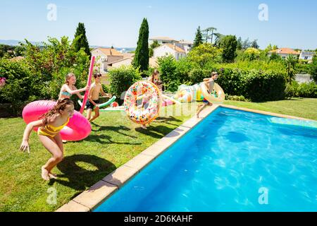 Group little kids run and jump into the swimming pool holding inflatable toys diving in the water - Stock Photo