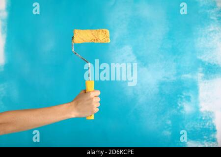 close up of female hand holding paint yellow roller over blue background-repair, construction and building tools concept. Convenient and versatile