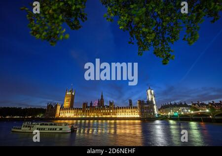 Houses of Parliament in Westminster, London, UK. View across the Thames with Westminster Bridge. Boat in foreground and long exposure motion blur.