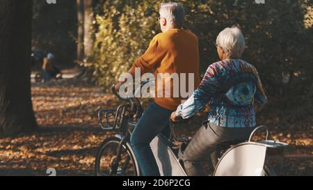 Senior couple riding double bicycle in autumn. Grandmother and grandfather cycling together . Elderly people healthy and active lifestyle. High quality photo