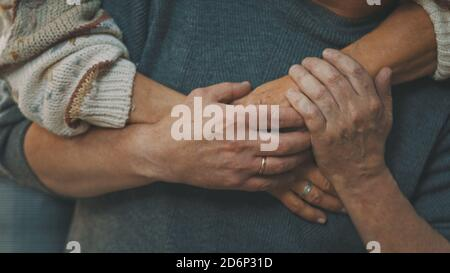 close up wrinkled hands. Happy old couple hugging in park. Senior man flirting with elderly woman. Romance at old age dancing on autumn day. High quality photo