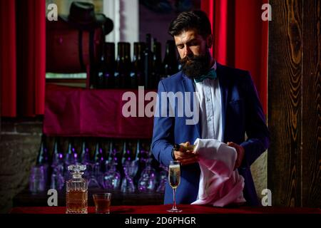 Barman pouring champagne in champagne glass. Alcohol concept. - Stock Photo
