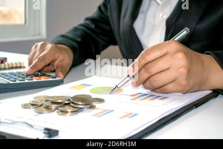 Close-up of women using calculators to create accounting reports by the window in their own homes, cost calculation concepts, and work at home concept - Stock Photo