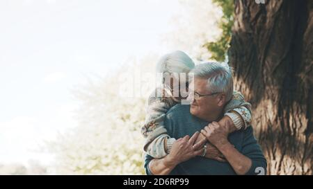 Happy old enjoying day in park. Senior man flirting with elderly woman. Dance in autumn day. High quality photo