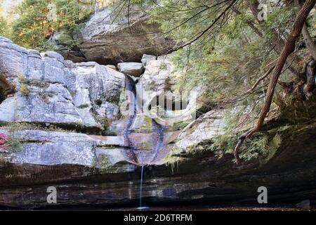 Fall scene at Cedar Falls in hocking hills ohio. Low water but full of orange leaves from autumn - Stock Photo