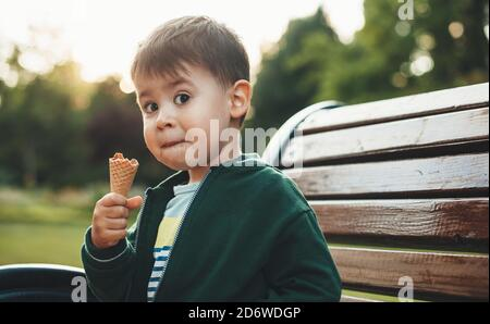 Cute boy is eating ice cream and looking surprised at camera while sitting on the bench in park