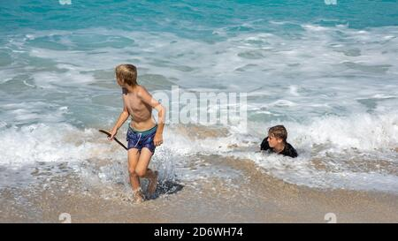 Frederiksted, St. Croix, US Virgin Islands-December 22,2019: Tourists bodysurfing at Sandy Point beach with blue Caribbean Sea waters on St. Croix