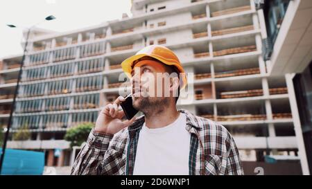 Caucasian male construction worker in orange hard hat and plaid shirt talking on phone at construction site. Architecture theme. Male profession - Stock Photo