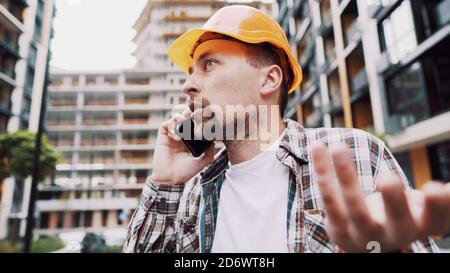 Engineer talking on phone. Architect using phone on construction site. Foreman phone call control process. Construction worker communications in - Stock Photo