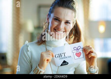 smiling middle age woman in white sweater and skirt in the modern house in sunny winter day showing gift certificate.
