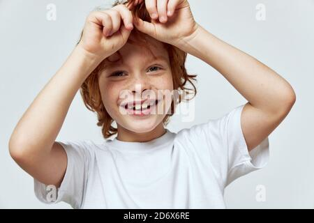 Smiling redhead boy holding hands near his head smile white T-shirt childhood  - Stock Photo