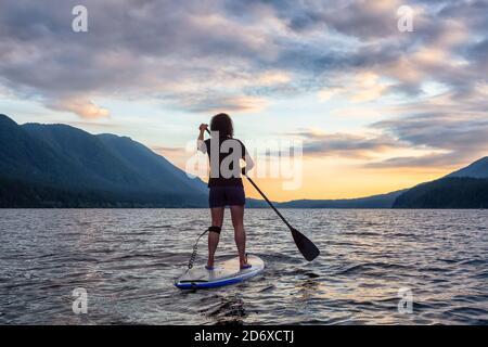 Woman Paddleboarding on Scenic Lake at Sunset