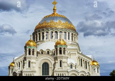 The domes of the Naval Nikolsky Cathedral with gilding and crosses in the city of Kronstadt against the background of a gray cloudy sky on a summer da