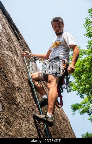 View to man rock climbing on rocky wall in the rainforest, Rio de Janeiro, Brazil - Stock Photo