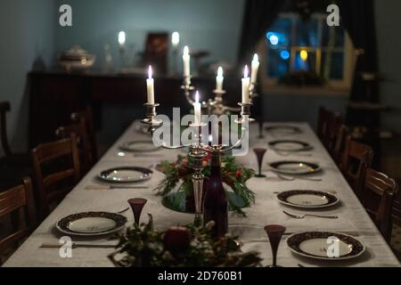 A dark romantic formal dining room table set with vintage china plates, silver candelabras with white lit candles, a white tablecloth, floral - Stock Photo