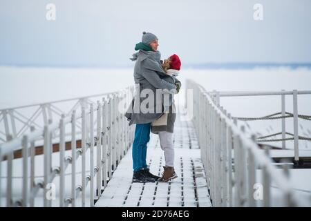 A beautiful woman and a beautiful man left their children at home and went for a walk together along the river on the pier.