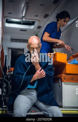 Injured man in a blanket breathing through an oxygen mask in an ambulance car, nurse searching for something in her medical kit in the background.