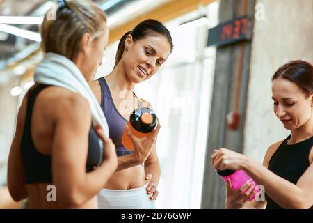 Healthy lifestyle. Group of three young beautiful fitness women resting after workout, talking and discussing sport results while standing at gym. Workout, training and healthy lifestyle