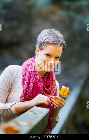 Charming charismatic photogenic appealing Portrait isolated hand hold holding fallen leaf Fall Autumn in country-side countryside countrygirl teengirl - Stock Photo