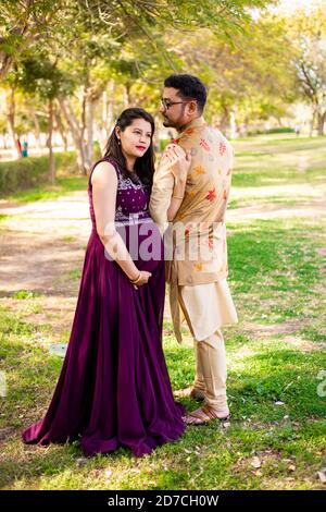 Young asian indian pregnant woman with her husband wearing traditional outfit standing in park or garden copy space to write text.
